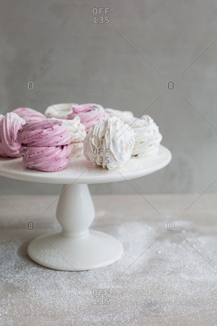 Soft fluffy zefir with a dusting of powder sugar on cake stand