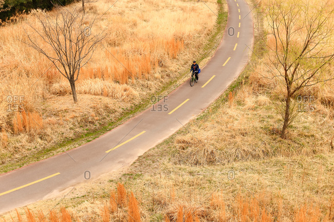 At Taehwagang Park, Taehwagang, Jung-gu, Ulsan, Korea - March 18, 2018: A bicyclist on the park trail