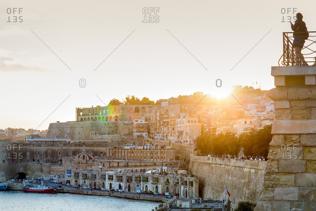 October 28, 2017: Person photographing the Grand Harbour in Valletta at dusk. Valletta, Malta, Mediterranean, Europe