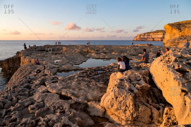 November 2, 2017: People enjoying sunset at Dwejra Bay on the rugged Gozo coast, Malta, Mediterranean, Europe