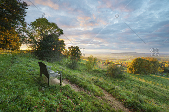 Cotswold Way path and bench with views to the Malvern Hills at sunset, Ford, Cotswolds, Gloucestershire, England, United Kingdom, Europe