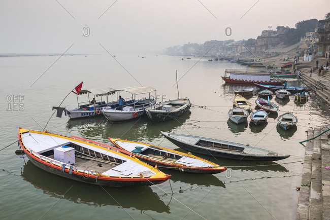 January 5, 2017: Boats in the mist at dawn on the River Ganges, Varanasi, Uttar Pradesh, India, Asia