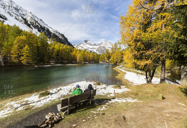 People on a bench on the shore of Lai da Palpuogna (Palpuognasee), Bergun, Albula Pass, Canton of Graubunden (Grisons), Switzerland, Europe