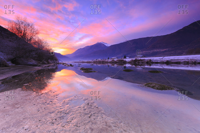 The colors of sunset are reflected in the Adda River, Valtellina, Lombardy, Italy, Europe
