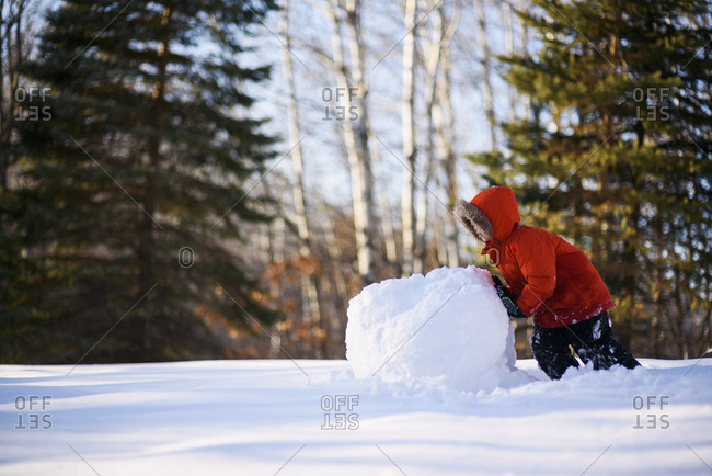 Little boy building a snow man