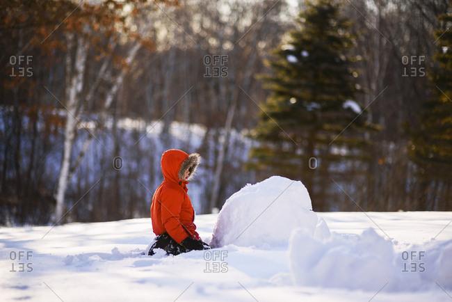 Boy building a snow man