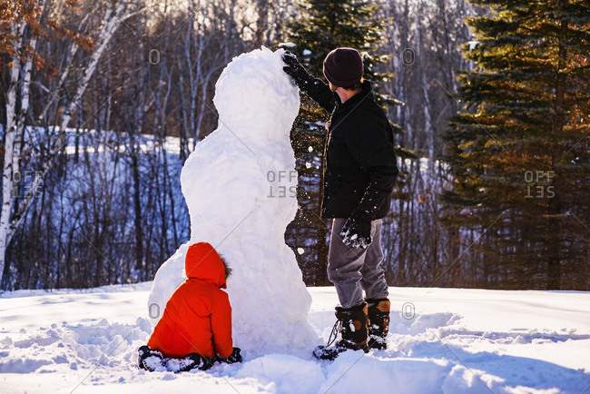 Little boy building a snow man with his father