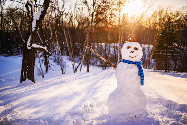 Snowman wearing blue scarf in sunset light