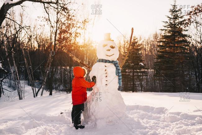 Little boy building a snow man at sunset