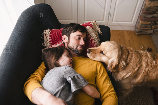 Dog watching father and daughter cuddle on a couch