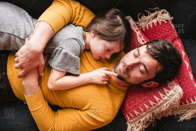 Overhead view of father and daughter cuddling on a couch