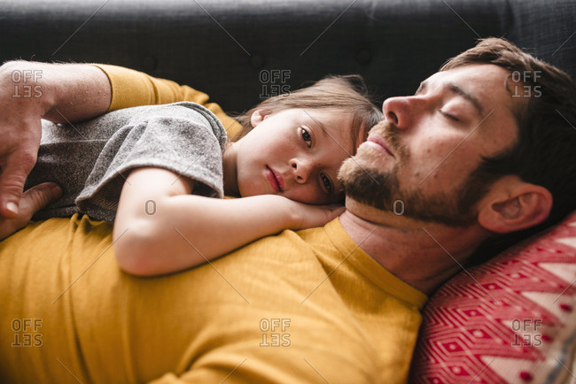 Father and daughter cuddling on a couch