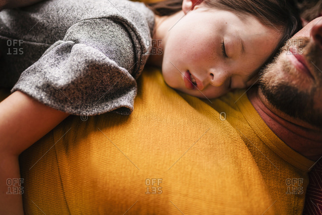 Close up of father and daughter sleeping on a couch