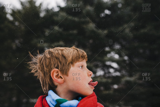 Boy wrapped in a blanket outside catching snowflakes