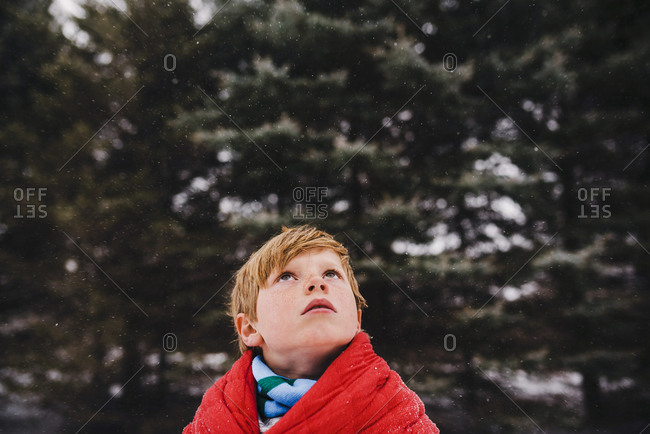 Boy wrapped in a blanket outside looking up at the snowfall