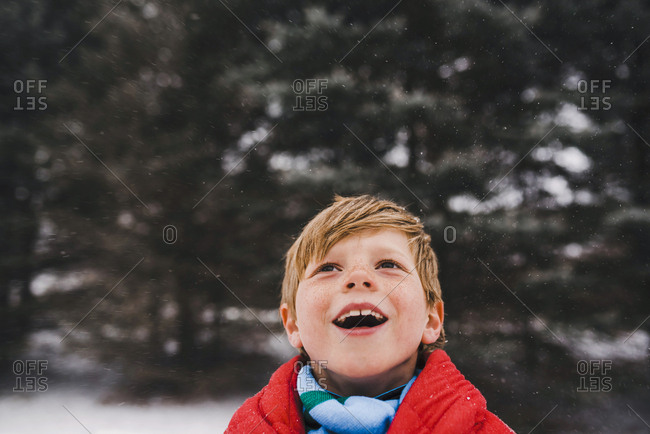 Boy wrapped in a blanket outside looking up at the snowfall with a smile