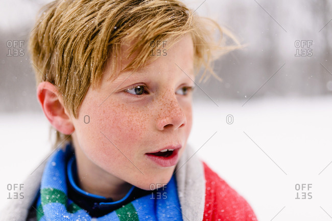 Close up of a young boy with red blanket in the snow