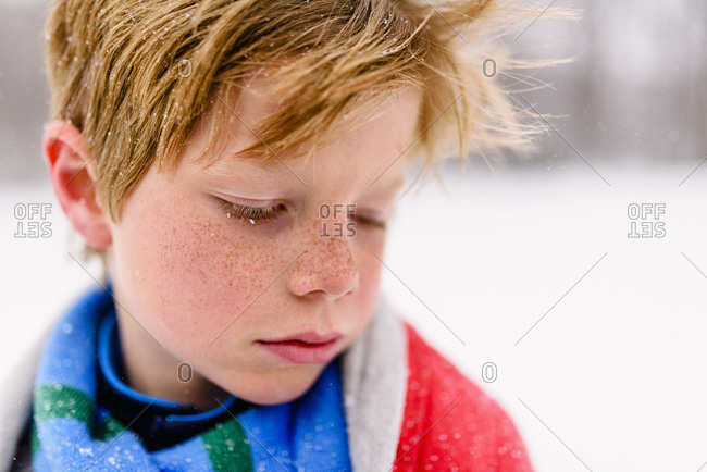 Close up of a boy with red blanket in the snow