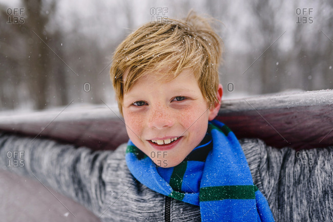 Young boy with blanket playing in the snow