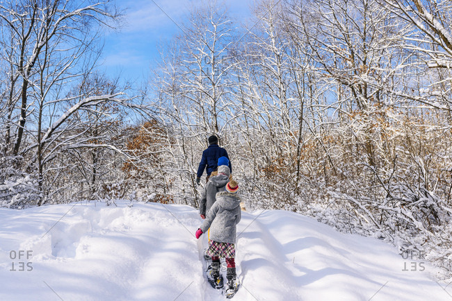 Family with young kids outside in the winter with snow shoes walking uphill