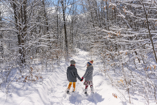 Two little kids holding hands outside in the winter with snow shoes