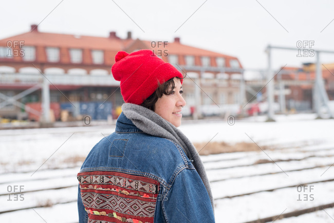 Woman outside in winter wearing red hat and jean jacket