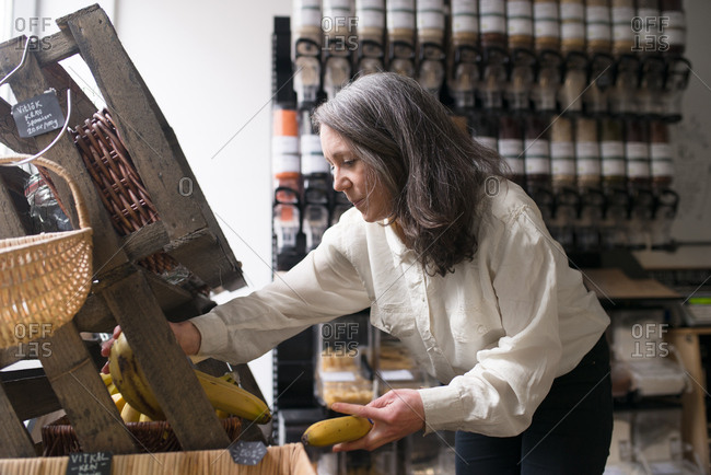 Woman stocking bananas in small local grocery store