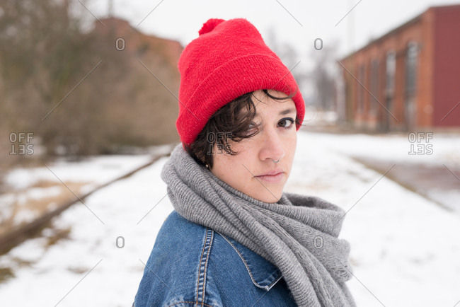 Woman outdoors in winter wearing red hat and jean jacket