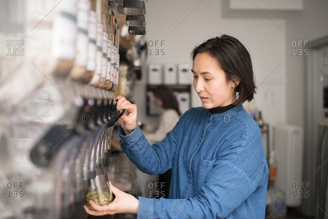 Young woman pouring seeds into jar in a small grocery store