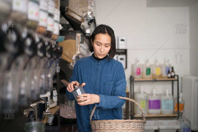 Young woman closing lid to jar in a small grocery store