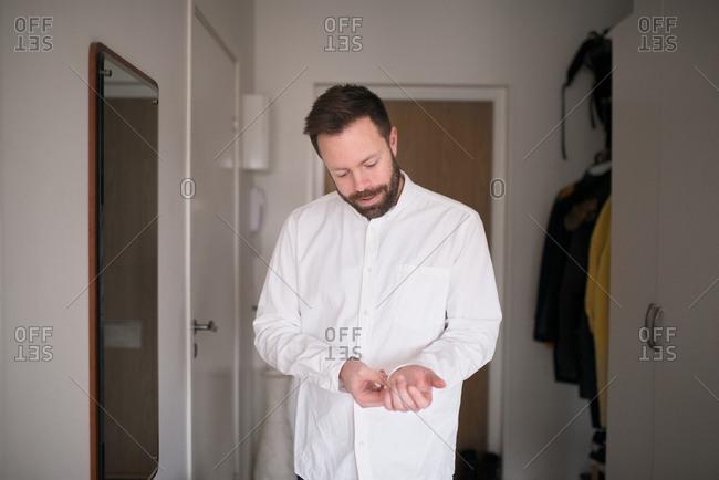 Man buttoning sleeve of white shirt