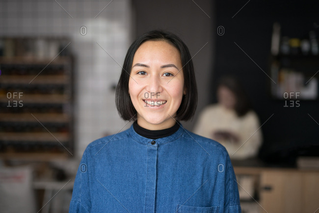 Portrait of young Asian woman in a grocery store smiling
