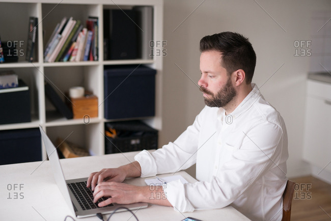 Man typing on laptop computer in home office