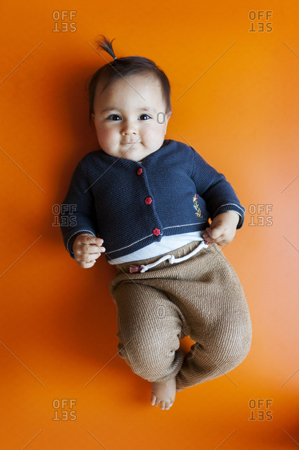 Happy baby in cute outfit lying on vibrant floor