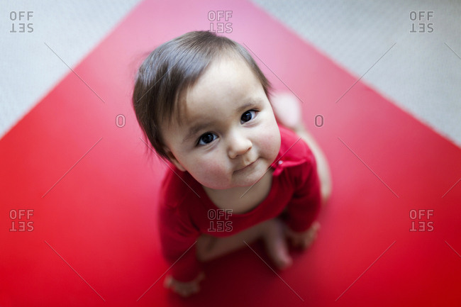 Portrait of a baby sitting on floor looking up