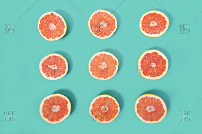 Nine halved grapefruits arranged on a cool solid background