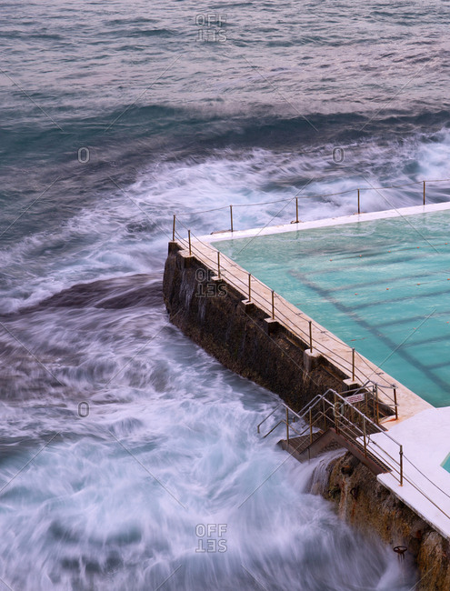 Motion blurred waves at Bondi beach ocean pool in the early morning