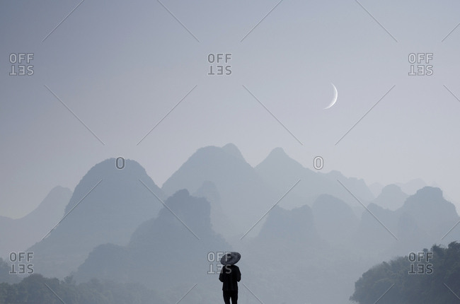 Lone farmer enjoying view of foggy mountains and a sliver of the moon in China