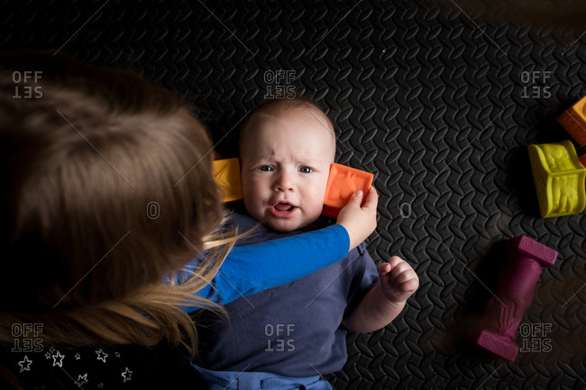 Sister playing with blocks on baby brother's ears