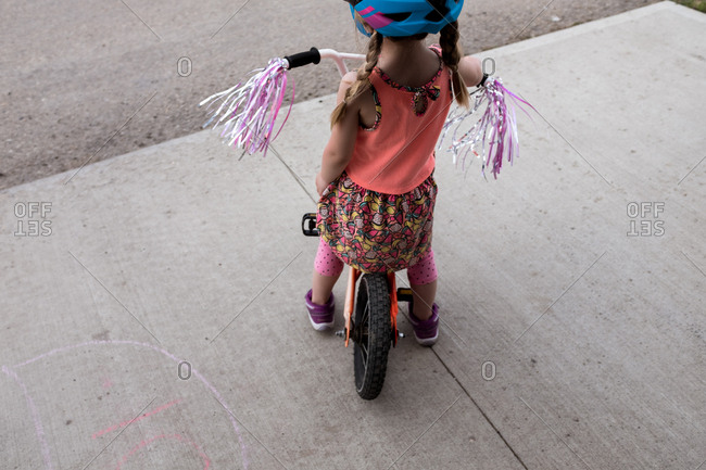 Young girl sitting on parked bike with handle streamers