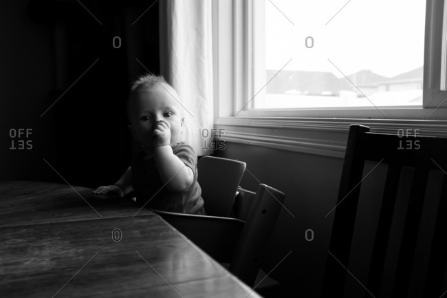 Portrait of baby boy sitting in high chair at dining table