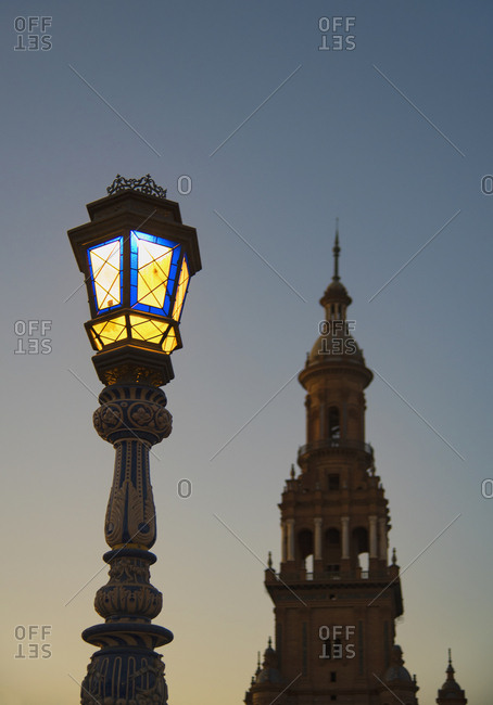 October 5, 2017: Spain, Andalusia, Seville, Plaza de Espana, Illuminated old fashioned street lamp and tower at dawn