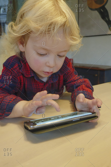 Little boy (2-3) playing game on smart phone