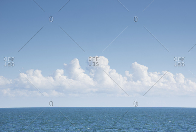 White cumulus clouds above blue Atlantic Ocean