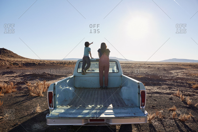 USA, Arizona, Mother with son (6-7) standing on pick up truck parked in desert landscape