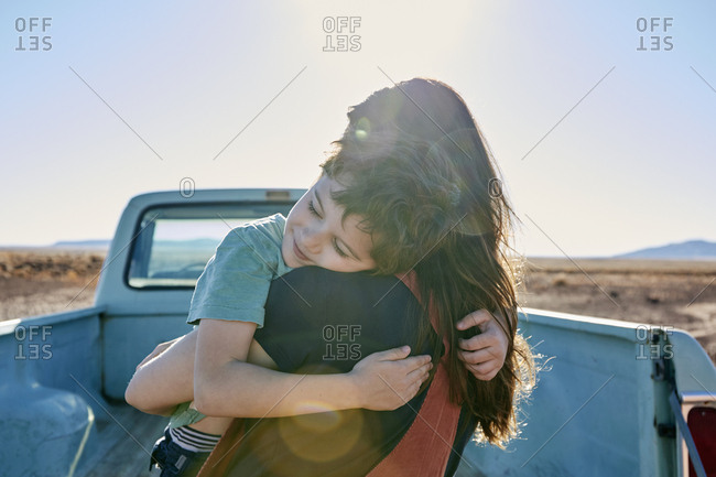 USA, Arizona, Mother with son (6-7) embracing on pick up truck parked in desert landscape