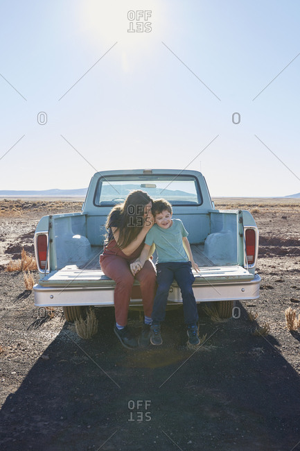 USA, Arizona, Mother with son (6-7) sitting on tailgate of pick-up truck