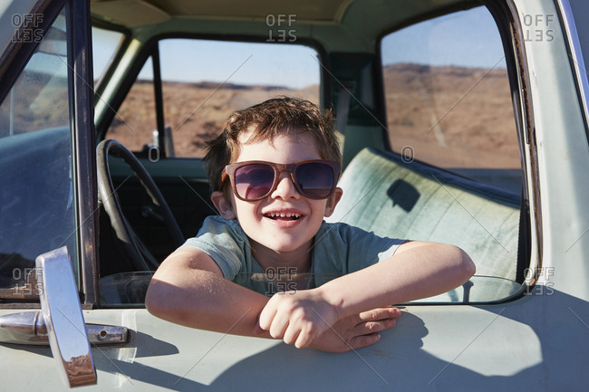 USA, Arizona, Portrait of smiling boy (6-7) sitting in pick-up truck