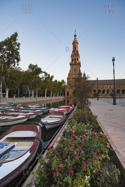 Spain, Andalusia, Seville, Rowboats moored in canal on Plaza de Espana at dawn