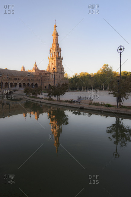 Spain, Andalusia, Seville, Tower in Plaza de Espana reflected in water
